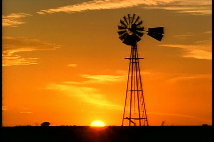 Old Farm Wind Pump With Sun Setting Into The Horizon In