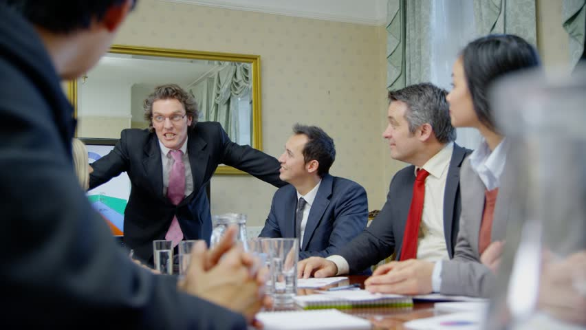 Happy and enthusiastic business team of mixed ages and ethnicity are seated around a conference table for a business meeting. They reach across the table to shakes hands with one another. Slow motion.