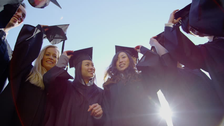 Graduation caps are tossed into the air by a happy group of friends on a bright sunny day. In slow motion. with flare.