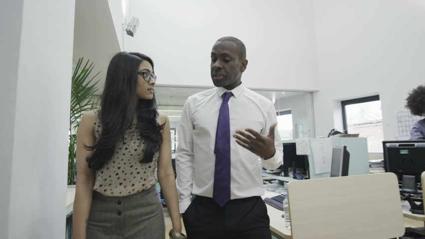 Businessman and woman talking together as they walk around a busy office with many workers. Could be collaborating on a project, or an office manager interviewing a candidate for a job. In slow motion