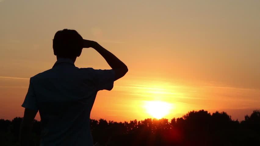 Plane flies over a man standing in dusk light