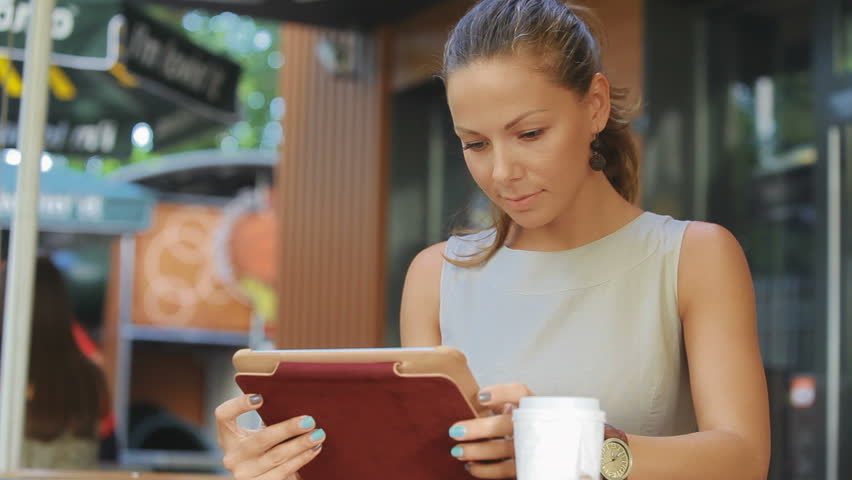 Young business woman sits at a table at a fast food restaurant. She carried a tablet with access to the Internet, it checks the mail and drinking coffee. She looks very happy