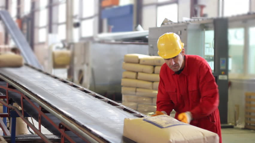 Worker controls sacks of sugar on the conveyor belt in a sugar factory - HD stock footage clip