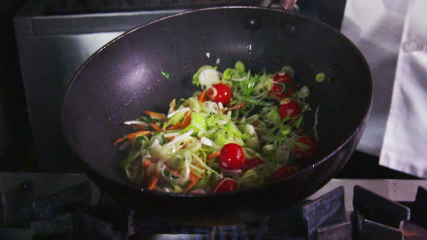 A stir fry meal being prepared in a hotel or restaurant kitchen flambe style. No faces can be seen.