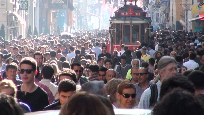 ISTANBUL, TURKEY - 13 APRIL 2013: People walk through one of the busiest shopping streets in Istanbul, while a tourist tram tries to make its way through the crowd