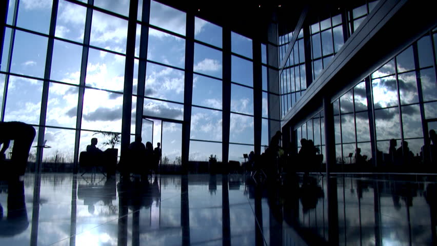 Time lapse with business group silhouetted in modern office building or airport - Clouds and business people rushing by. High quality HD video footage