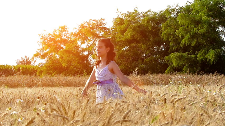 Little girl running cross the wheat field at sunset.High speed camera,slow motion.
