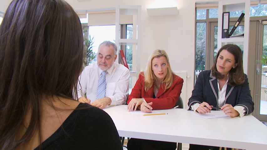 Young female candidate for a job is interviewed by three employers. High quality HD video footage