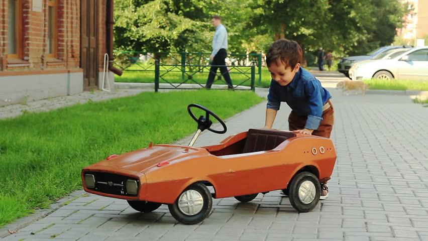 The three-year old boy riding a toy car