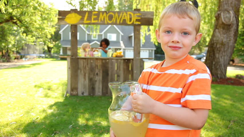 Young boy in front of lemonade stand