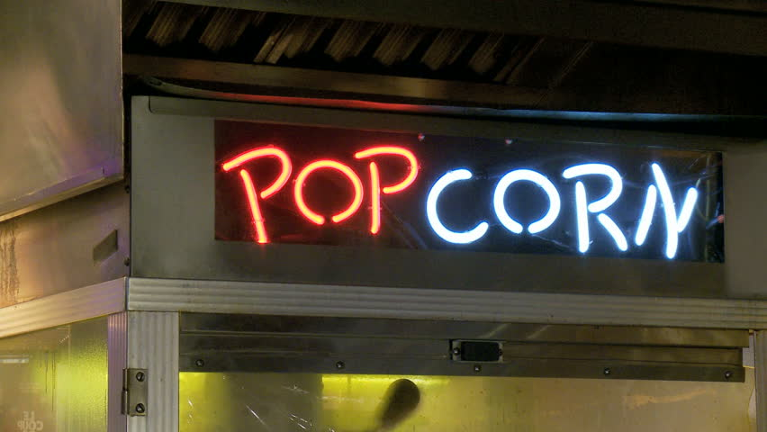 """Movie theatre commercial popcorn machine with a neon sign that says """"POPCORN""""."""
