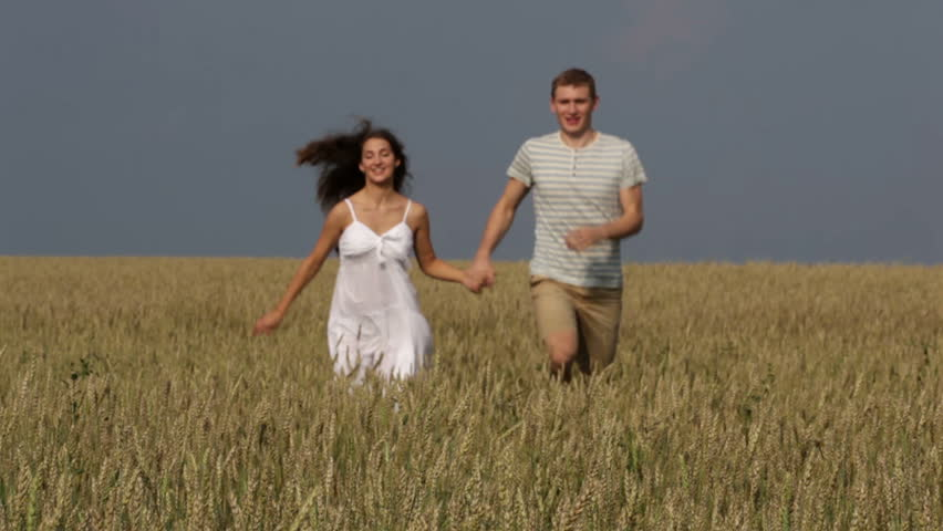 Happy Rural Couple Running Across The Field Holding Hands