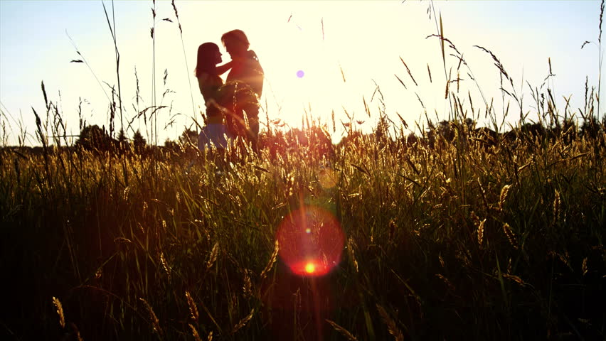 A silhouetted couple hug, kiss and then walk in a wide open golden field at sunset