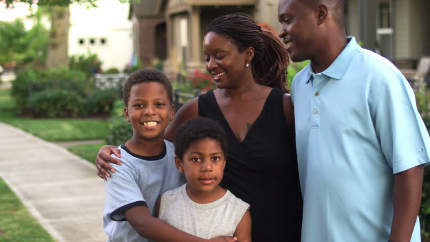 A cute African American family stands outside of a house and smiles for the camera. Medium shot