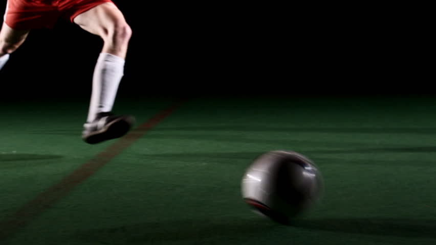 Soccer player runs in and kicks the ball. Medium shot - HD stock video clip