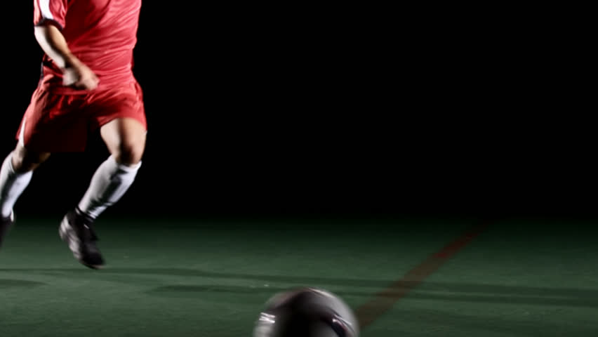 A soccer, or football, player that is dramatically and artistically lit, on an artificial field pitch on a black background, runs up and kicks a ball hard in slow motion - HD stock footage clip