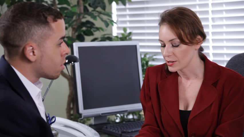 A lovely redheaded business woman talking to or interviewing a young man across the desk from her.