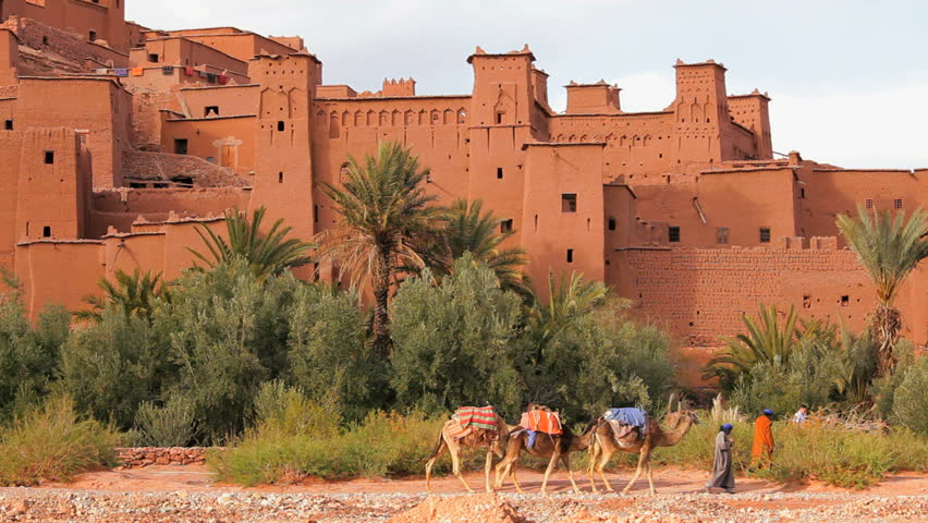 A group of men with camels and a tourist walk outside the fortified town of AitÊ Benhaddou in the High Atlas Mountains of Morocco