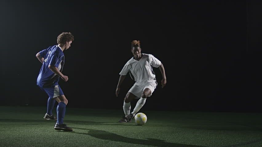 A soccer player dribbles the ball and attacks a defender