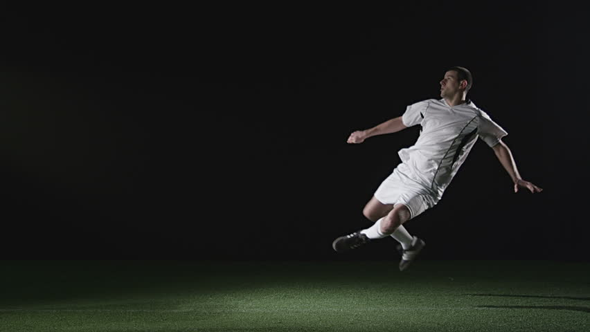 A soccer player jump kicks a ball while it's still in the air. Wide slow motion shot.