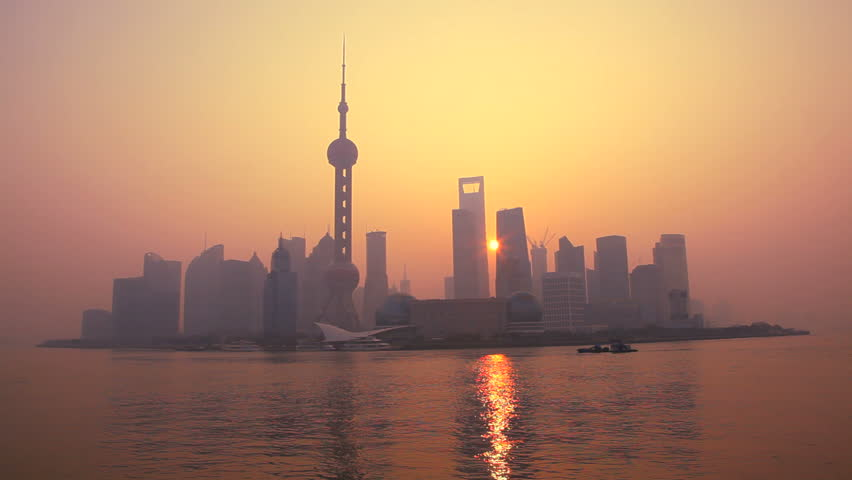 China - January 2012: Warm tone view of sunrise behind modern Shanghai cityscape with Oriental Pearl Tower, Huangpu River, Pudong district in Shanghai, China in January, 2012