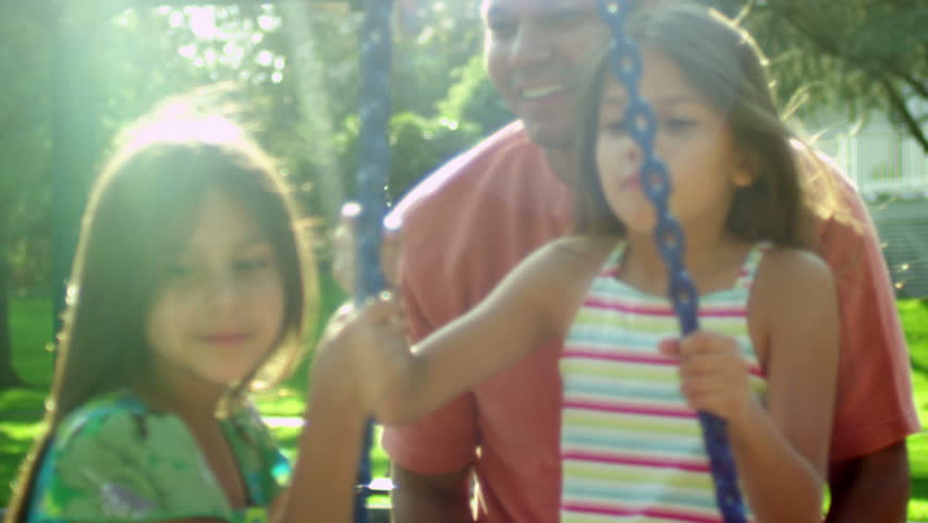 Father pushes his two daughters on a tire swing in a park. Medium shot.