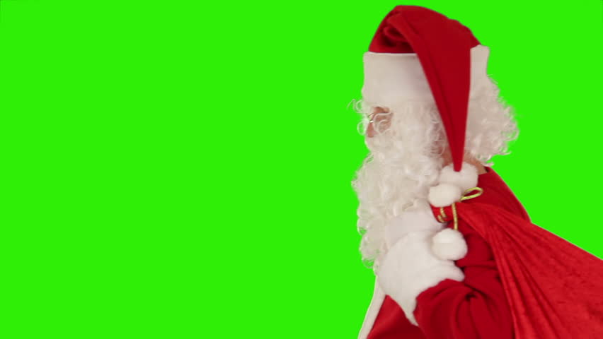 Santa Claus carrying his bag, is looking at camera, sends a kiss and wave, Green Screen - HD stock footage clip