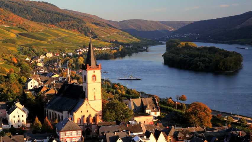 Scenic view with river ferry and church tower of the small rural town of Lorch with surrounding farmland in the Rhine Valley, Germany