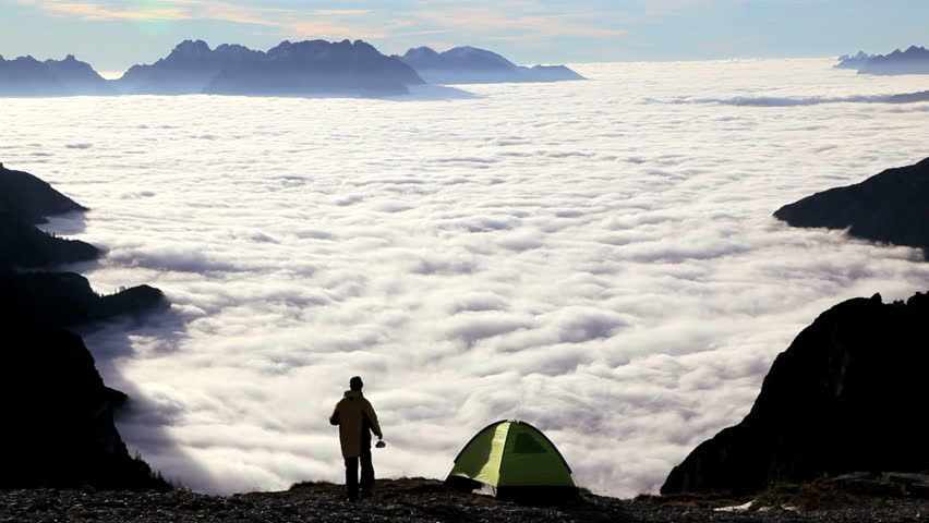 Camper pouring coffee and preparing to hike above the clouds with a view of the distant peaks of the Italian Dolomites