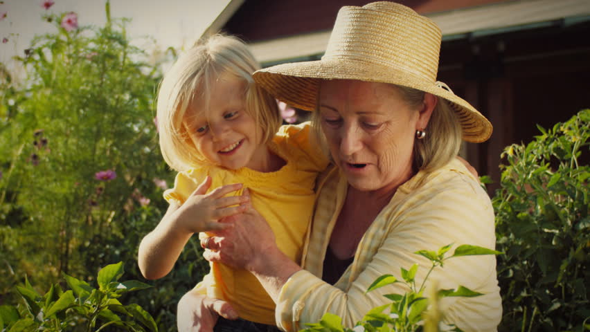 A little blonde girl runs to her grandmother's arms in a garden.