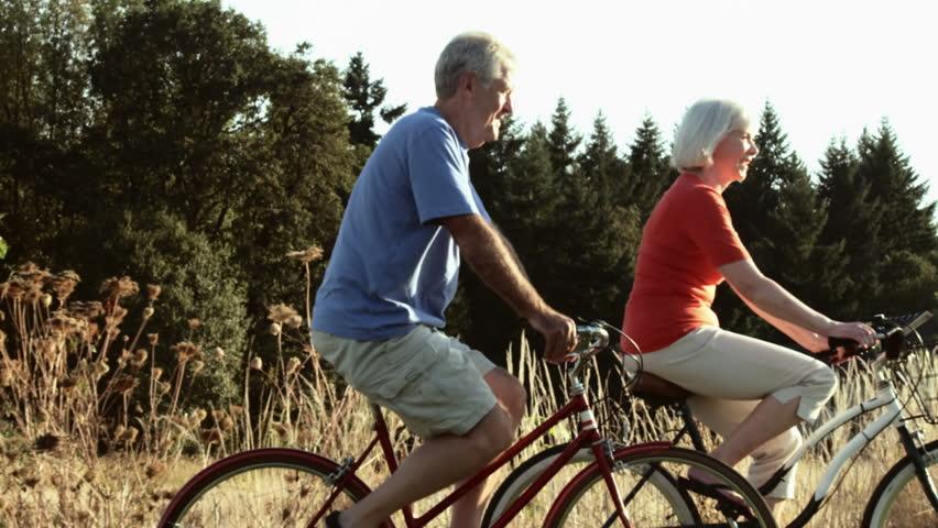 Senior couple enjoy time together bike riding. Wide shot.