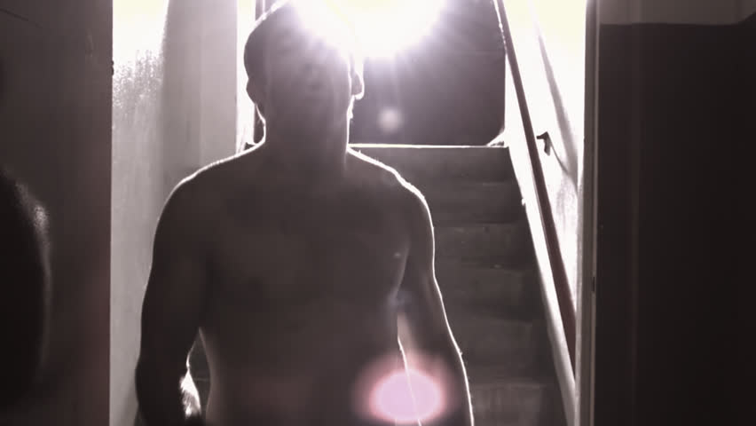A fighter walks down a hallway towards the camera punching, with a bright light behind him and lens flare - HD stock video clip