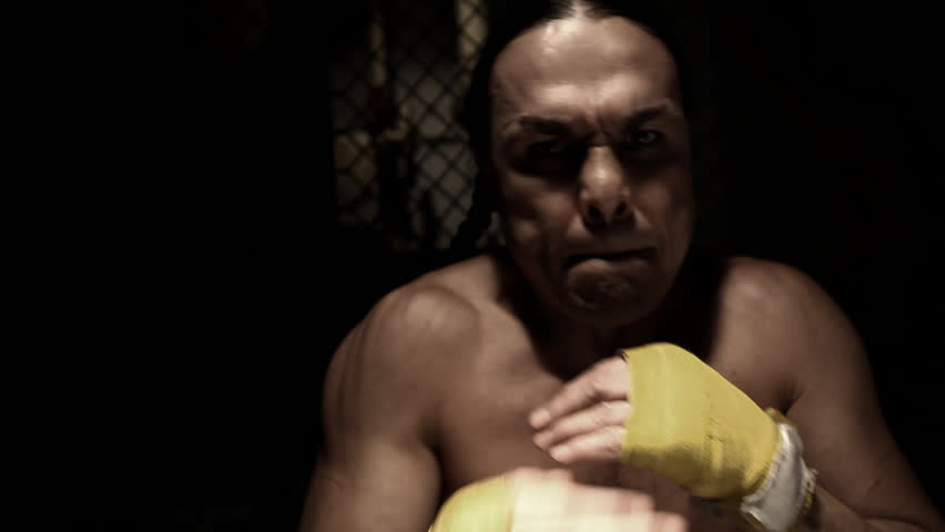 A Native American athlete intimidates the camera by shadow boxing in front of it. Medium shot. - HD stock video clip
