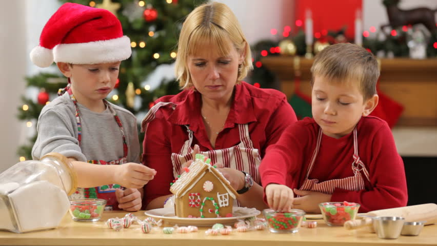 Mother and kids decorate Gingerbread house for Christmas