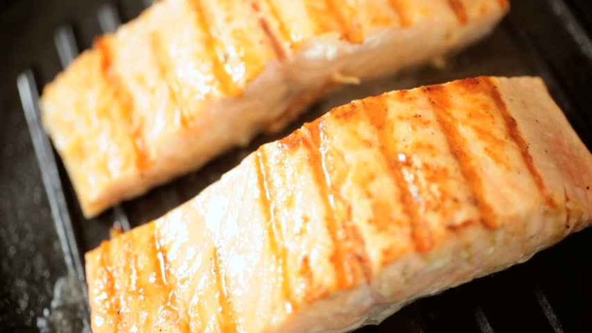 Fresh Sockeye salmon steaks being cooked on a griddle pan close up