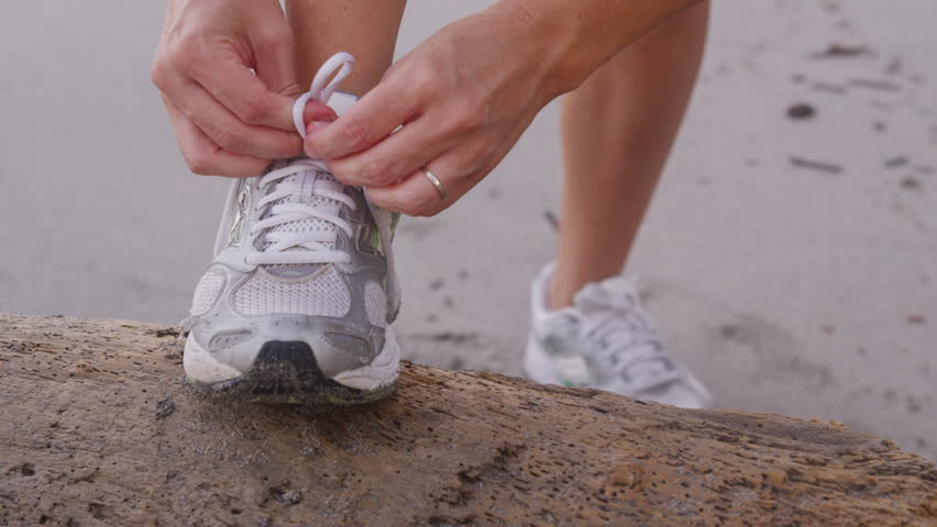 Closeup of woman tying running shoe at beach