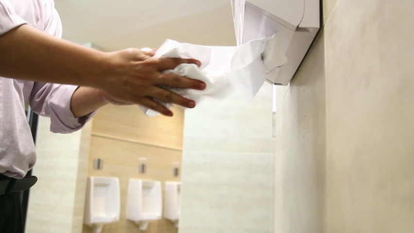 Office man drying hands with paper towels in a bathroom.