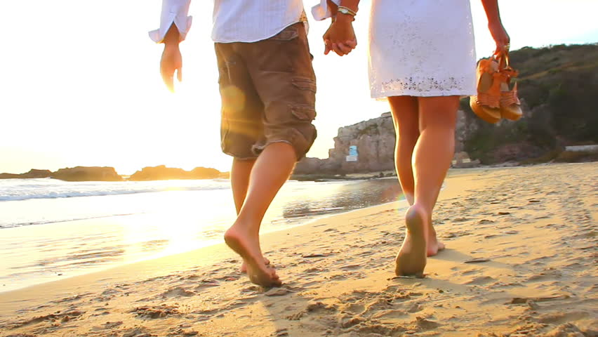 An older couple holds hands and walks down the beach at sunset getting their feet wet