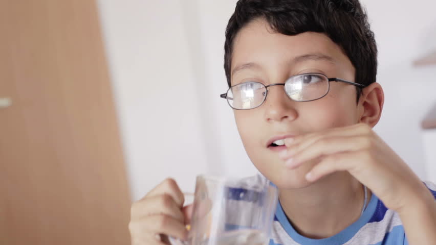 close up of a boy with glasses drinking a glass of water at the dinner table at home