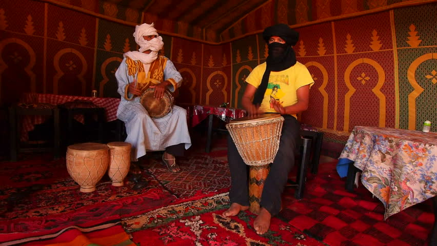 ZAGORA DESERT, MOROCCO, MAY 04: Unidentified Berber men playing the drum inside of the tent on the Zagora Desert in Morocco, May 04, 2013. Berber people live on the desert as a hundred years ago.