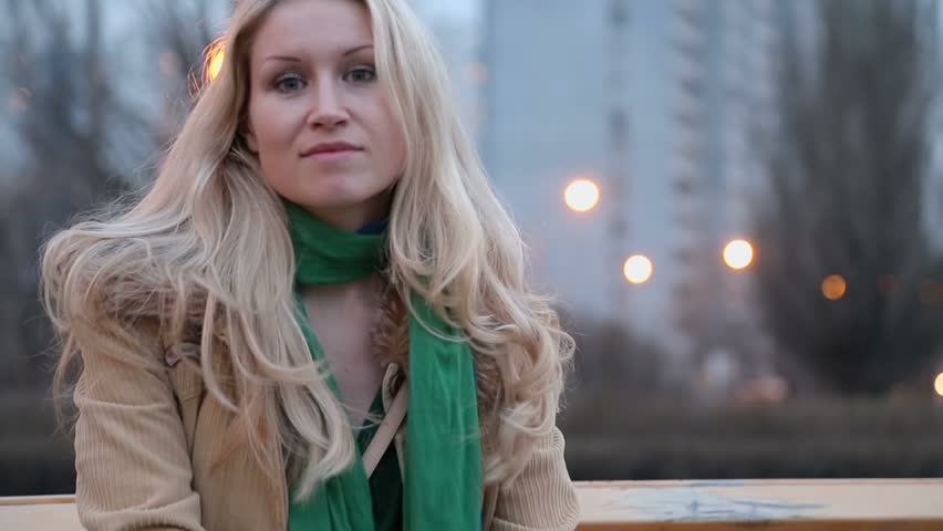 Cute blonde girl in jacket smiles at evening in city - HD stock video clip