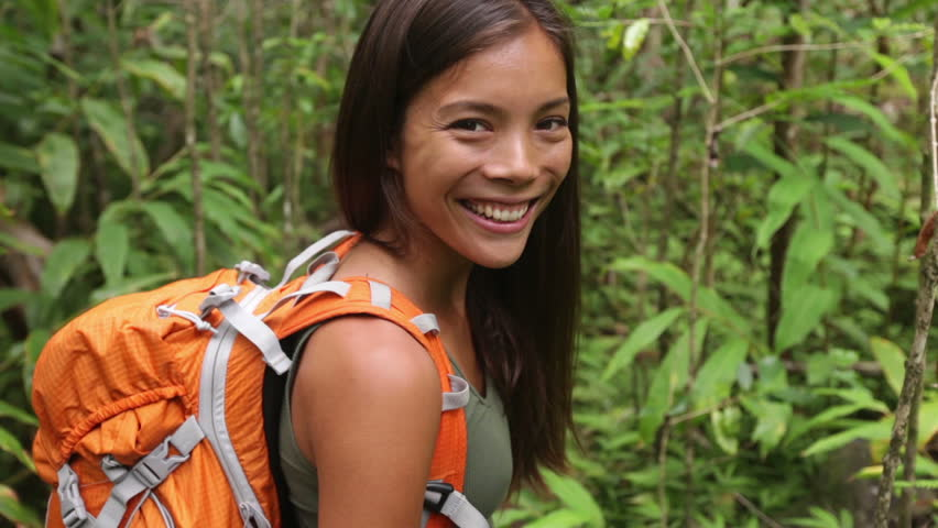 Hiking woman gesturing come along follow me, waving and hand looking at camera. Young female hiker walking with backpack in rain forest nature on Maui, Hawaii, USA. Mixed race Asian Caucasian girl.