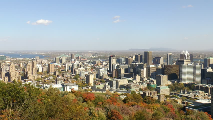 Aerial View Of Montreal downtown skyline as seen from the lookout at Mount Royal, the St Lawrence River is visible in the distance which is part of the St Lawrence Seaway.