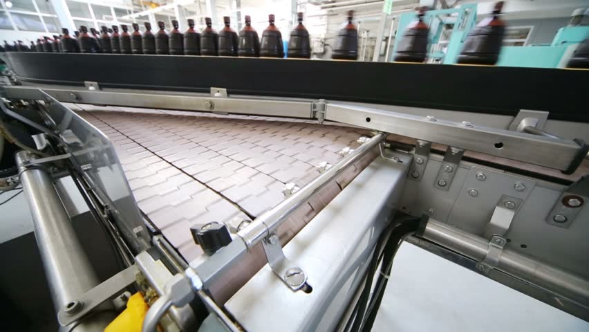Filled brown bottles with liquid moving on production line