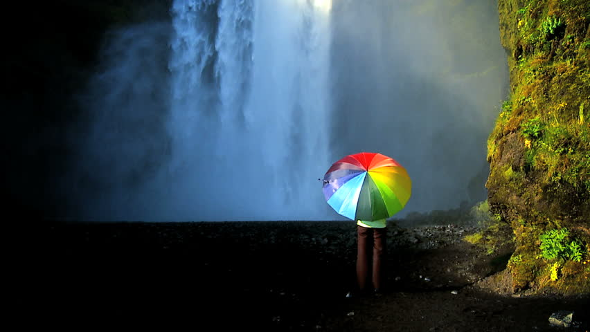 Concept shot of lone female standing on the edge of a waterfall with rainbow umbrella to shelter from changing climate conditions  60 FPS - HD stock footage clip