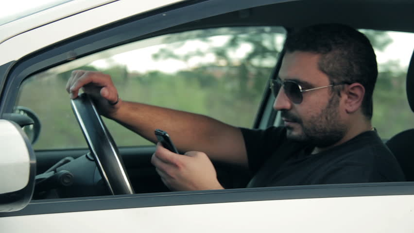 Irresponsible man driving car and speaking on mobile phone