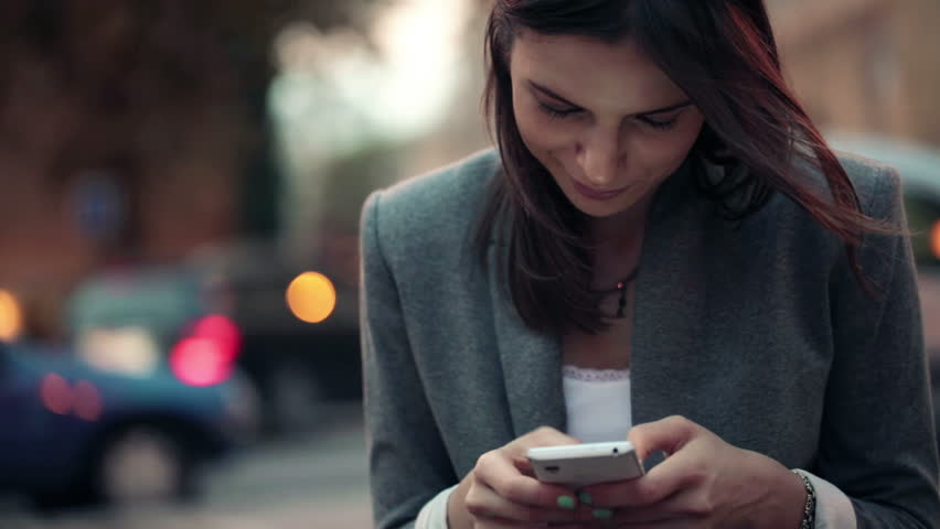 Elegant beautiful woman texting on smartphone in the city