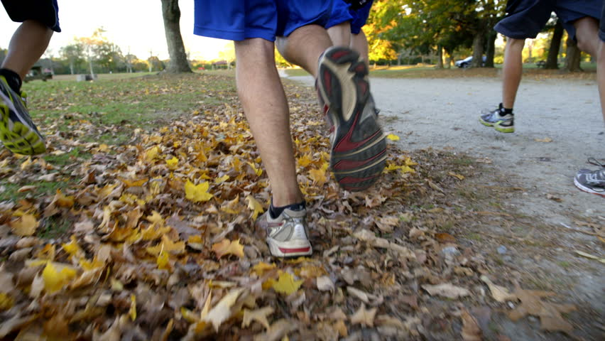 Legs of runners in park with dirt path and fall leaves. 240 fps slow-motion.