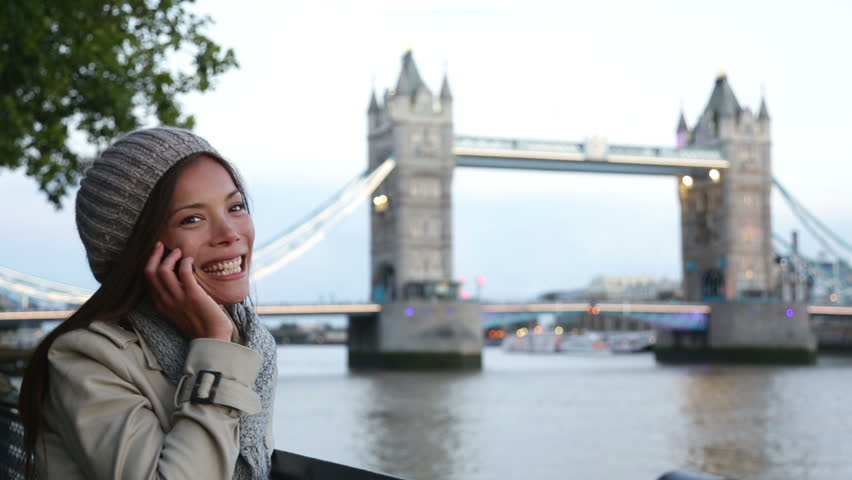 Cell phone - woman talking on smartphone in London by Tower Bridge. Casual young professional smiling laughing having conversation on mobile phone by the River Thames, London, England, United Kingdom.