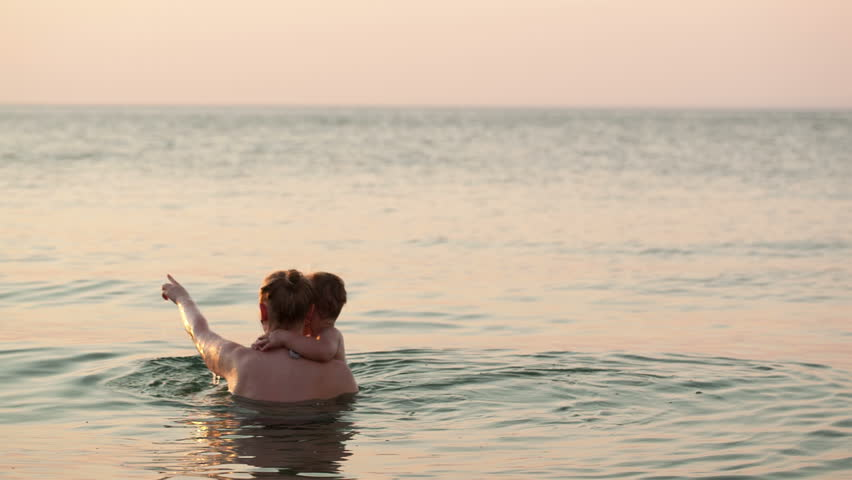 Loving mother and her young child bathing in the sea water by the beach in the sunset - HD stock footage clip